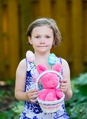 picture of bunny rabbit  - A portrait of a happy little girl in a dress holding a basket with a pink bunny rabbit and colorful Easter eggs outside in a garden during the spring season - JPG