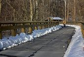 image of covered bridge  - walkway with a railing on a bright snowy cold winter day at the park with a walker going toward a covered bridge - JPG