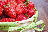 image of wooden basket  - Fresh ripe strawberries in basket on a brown wooden background - JPG