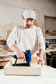 stock photo of workplace safety  - Carpenter working assembling a drawer with a screwdriver - JPG