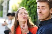 stock photo of angry man  - Woman trying to kiss a man and he is rejecting her outdoor in a park - JPG