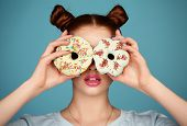 image of donut  - fashion studio photo of beautiful young girl with dark hair and bright makeup holding sweet donuts - JPG