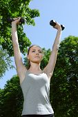 foto of light weight  - Sports woman doing exercises with light weights against a background sky and foliage - JPG