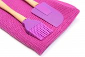pic of purple white  - Closeup of purple silicone kitchen accessories spatula and brush lying on purple cloth composition of colors purple - JPG