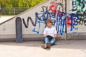 stock photo of skate  - boy resting with skate board at the skate park - JPG