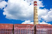 picture of hollow  - Chimney in brickyard factory with stack of red hollow - JPG