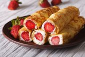 image of crepes  - Crepes with fresh strawberries and cream cheese on a plate - JPG
