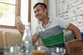 foto of internet-cafe  - Asian Man Using Cell Phone Smile Sitting at Cafe - JPG
