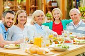 foto of family bonding  - Happy family of five people bonding to each other and smiling while sitting at the dining table outdoors - JPG