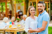 image of family bonding  - Happy young couple bonding to each other and smiling while their family sitting at the dining table in the background - JPG