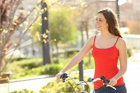 picture of candid  - Candid woman walking in an urban park in summer or spring carrying a bicycle - JPG