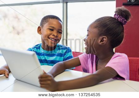 Smiling school kids using a digital tablet in classroom at school
