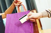 Close-up of man?s hand passing over credit card to shop assistant after shopping