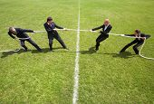 picture of tug-of-war  - Businessmen and businesswomen playing tug of war - JPG