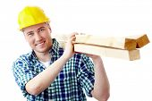 Portrait of a cheerful worker in helmet carrying lumber