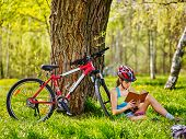 Bikes cycling girl. Girl rides bicycle. Girl in cycling read book on rest near bicycle. Cycling wear poster