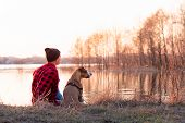 Young Man And Pet Dog Sit By Lake At Sunset In Spring Or Autumn. Male Person And Staffordshire Terri poster