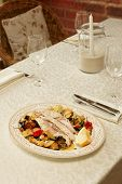 Sea bass fillet baked with vegetables, Italian dish, on restaurant table