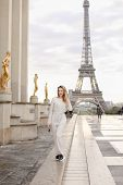 Lady In White Overalls Walking On Trocadero Square Near Gilded Statues And Eiffel Tower In Paris. Co poster