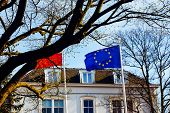Flag Of European Union Against Blue Sky Background. Landscape With A White House, Roof And The Flag  poster