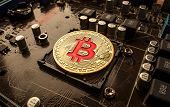 Gold Bit Coin BTC coins on the motherboard. Bitcoin is a worldwide cryptocurrency and digital paymen poster