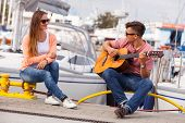 Love Romance Affection Music Sound Talent Concept. Girl Charmed By Musican. Young Guitarist Playing  poster