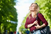 Happy restful girl with backpack looking at one of amusements while taking walk in one of modern the poster