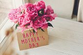 Happy Mothers Day Text On Craft Card And Pink Peonies Bouquet On Rustic White Wooden Window In Ligh poster
