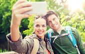travel, hiking, backpacking, tourism and people concept - smiling couple with backpacks taking selfi poster
