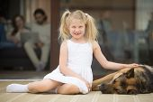 Smiling Girl Playing With Dog Outside Country House Looking At Camera, Little Kid Stroking Caressing poster