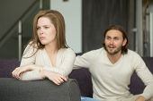 Unhappy Young Couple Arguing, Offended Affronted Woman Ignoring Angry Man Sitting Her Back To Jealou poster