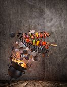 Kettle grill with hot briquettes, cast iron grate and tasty skewers flying in the air. Freeze motion poster