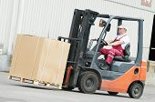 foto of forklift driver  - young cheerful warehouse worker driver in uniform driving forklift stacker loader - JPG