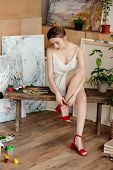 Beautiful Tender Young Woman Wearing Red Sandals In Art Studio poster