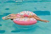 Smiling Girl In Bikini Enjoying Sunbath On The Inflatable Donut Mattress In The Swimming Pool On A H poster