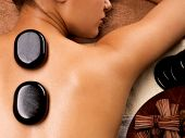 Portrait of young woman getting hot stone massage in spa salon. Beauty treatment concept.