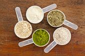 five plastic measuring cups of different superfood supplement powders (form bottom clockwise: wheatg