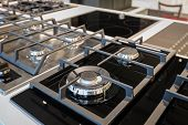 Gas stove with black glass tray selling in appliance retail store showroom, closeup poster