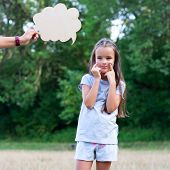 Pretty thinking little girl puts on a happy face, summer nature outdoor with cloud of thoughts (like poster