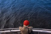 Unrecognizable Girl In A Brown Light Cloak With Her Back To The Viewer Looks At A Calm Endless Sea I poster