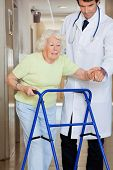 picture of zimmer frame  - Young male doctor showing way to the patient using walker - JPG