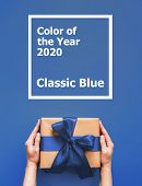 Female Hands Hold Gift Box On Blue Background With Words Color Of The Year 2020 Classic Blue. Gift B poster