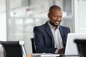 Positive mature businessman working on laptop in modern office. Successful african business man work poster