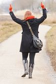 image of obscene  - Woman dressed in warm clothing making obscene gesture with fingers - JPG