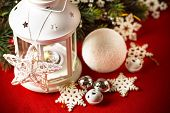 Magical white lantern is standing with beautiful white knit star on it and a fir tree branch and a s