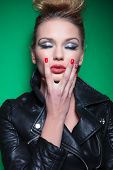 young beauty woman in leather jacket and beautiful make up touching her chin and keeps her eyes clos
