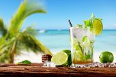 stock photo of mojito  - Mojito drink on wood with blur beach background - JPG