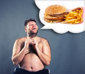 stock photo of big-foot  - Fat funny man dreaming about  hamburger - JPG