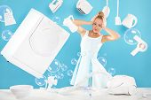 picture of stereotype  - young housewife standing on a blue background surrounded by white household appliances  - JPG