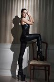 pic of latex woman  - Sexy woman in latex catsuit step on chair - JPG